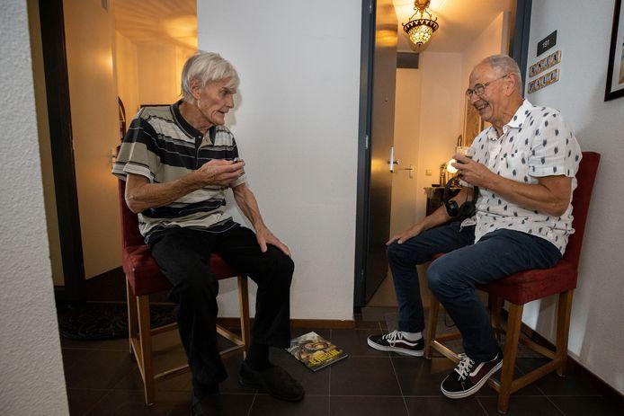 Jan Smit (links) en zijn buurman Paul Seesink tussen hun voordeuren in de gang van hun flat.