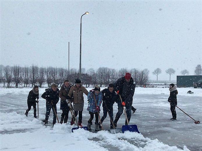 Vrijwilligers maakten dinsdag de nieuwe ijsbaan aan de Nieuwstraat sneeuwvrij.