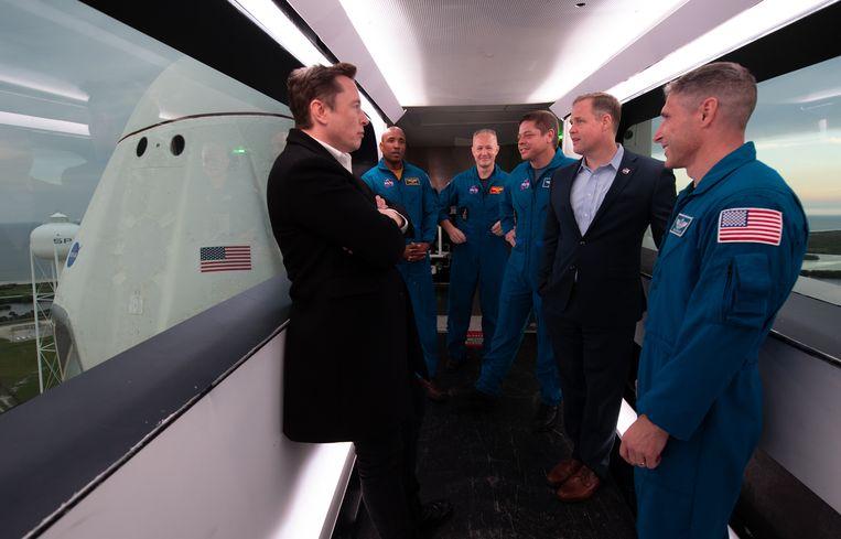 SpaceX-ceo Elon Musk (l.), astronauten Victor Glover, Douglas Hurley, Bob Behnken, NASA-directeur Jim Bridenstine en astronaut Mike Hopkins staan in de arm die toegang verleent tot de Crew Dragon tijdens een tour van de lanceerlocatie voorafgaand aan de onbemande 'Demo 1'-missie in 2019. Beeld (NASA/Joel Kowsky)