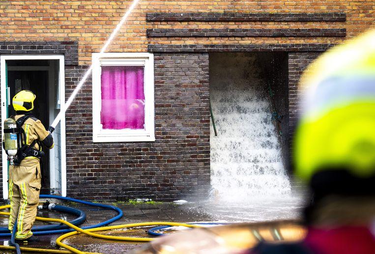 Brandweermannen in de Schilderswijk nadat er bij meerdere woningen een brand heeft gewoed. De brandweer is met groot materieel uitgerukt. Beeld ANP