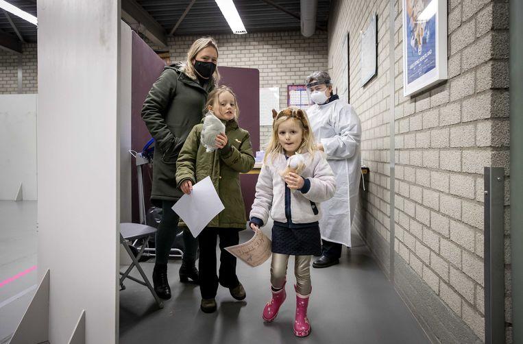Twee meisjes uit de gemeente Lansingerland krijgen een oorkonde en een knuffel na te zijn getest op het coronavirus. Beeld ANP
