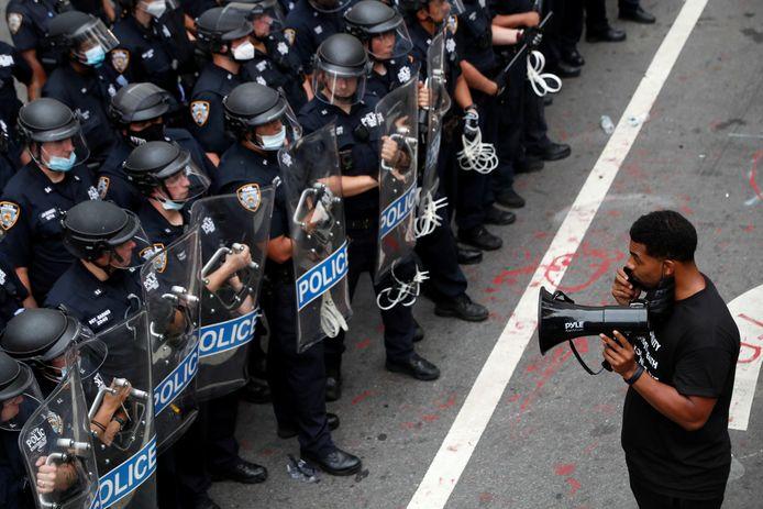 Een zwarte man demonstreert voor een groep gewapende politieagenten in New York. Archiefbeeld.