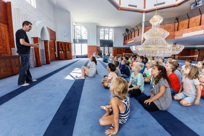 Kinderen luisteren geboeid naar de uitleg over de moskee in Roosendaal. foto marcel otterspeer/pix4profs
