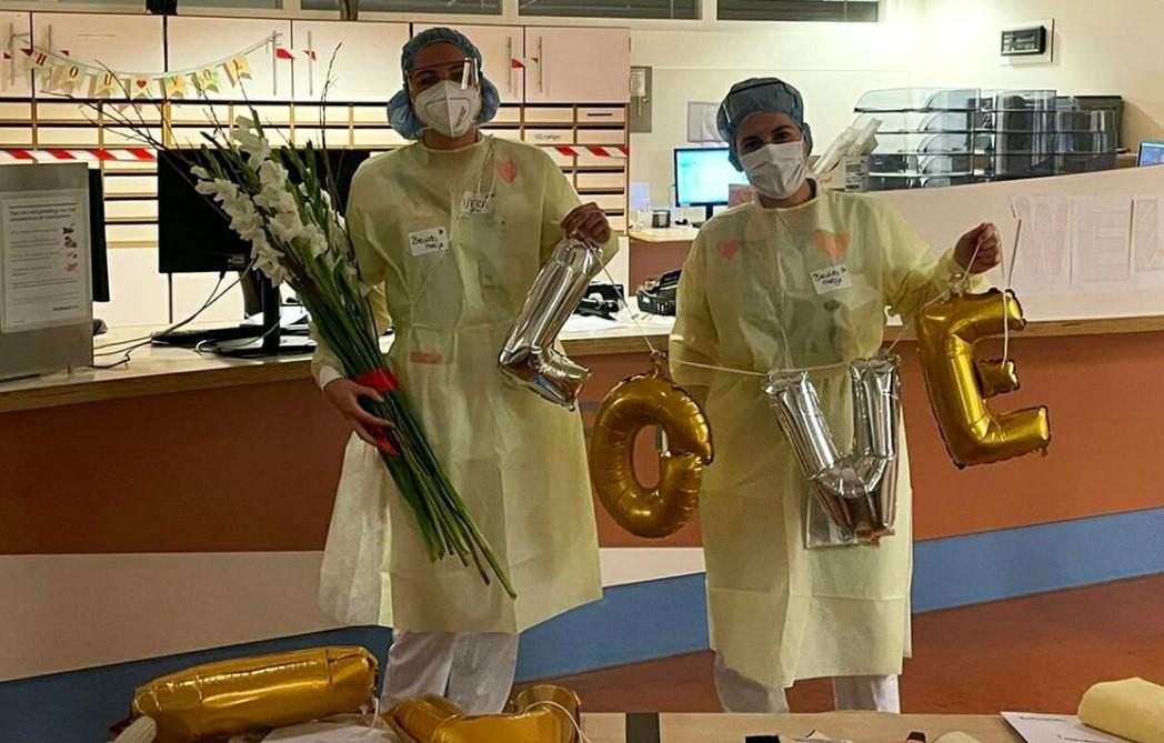 Verpleegkundigen met bloemen en ballonnen.