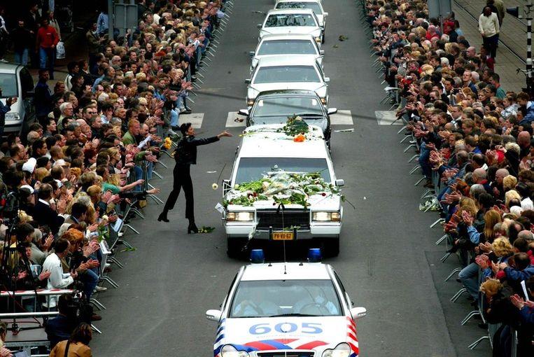 Een vrouw gooit bloemen op de auto met het stoffelijk overschot van Pim Fortuyn. Beeld ANP