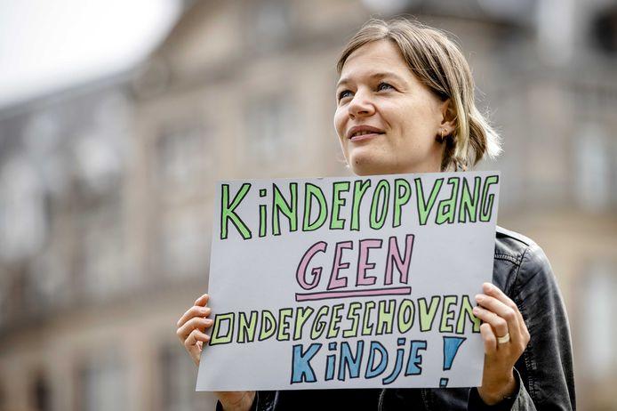 Een kinderopvangmedewerker tijdens een estafettestaking op de Dam in Amsterdam vanmorgen.