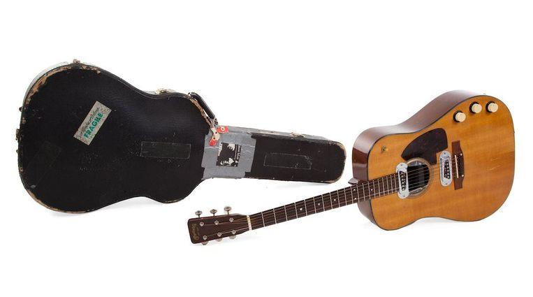 De Martin D-18E gitaar uit 1959, met de bijbehorende gitaarkoffer, wordt geveild met een startbod van één miljoen dollar. Beeld Photo News