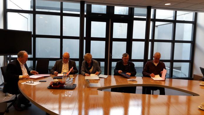 Wethouders Cees Liefting, Adri Totté, Chris van de Vijver, directeur Jan Loof van Leergeld en Leergeld-bestuurslid Mark de Bakker (vlnr) tekenen in het stadhuis van Terneuzen.