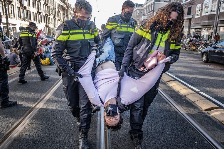 Politieagenten slepen klimaatactivisten van Extinction Rebellion weg tijdens een demonstratie in Amsterdam.  Beeld Joris van Gennip