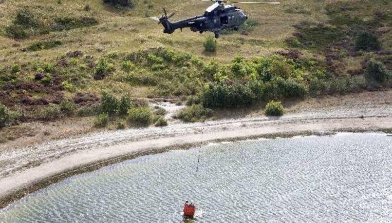 Een Cougar helikopter haalt zaterdag water uit een duinmeertje boven het verbrande duin rondom Schoorl. ( ANP) Beeld