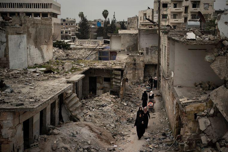 Vrouwen lopen door een zwaarbeschadigde wijk in Idlib, Syrië in maart vorig jaar. Beeld AP
