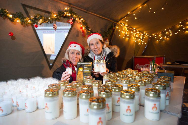 Renee Nacauder en Wendy Achtergael van de vrienden van de kerststal verkopen kaarsjes om aan te steken met het vredeslicht