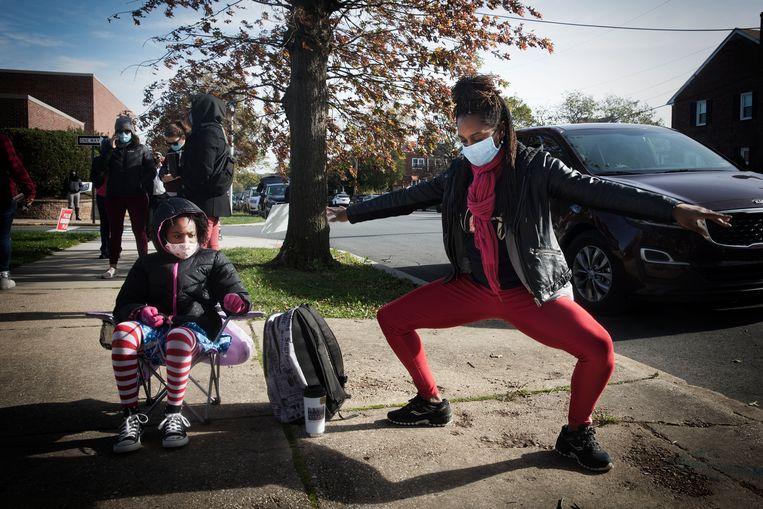 Danslerares Ashley Davis (37) staat met haar dochtertje Kennedy (8) in de rij om haar stem op Biden uit te brengen.   Beeld Daniel Rosenthal