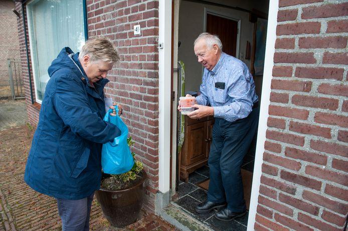 Vrijwilligster Sjan van Rooij overhandigt een maaltijd en soep aan Henk Kivits in Elshout.