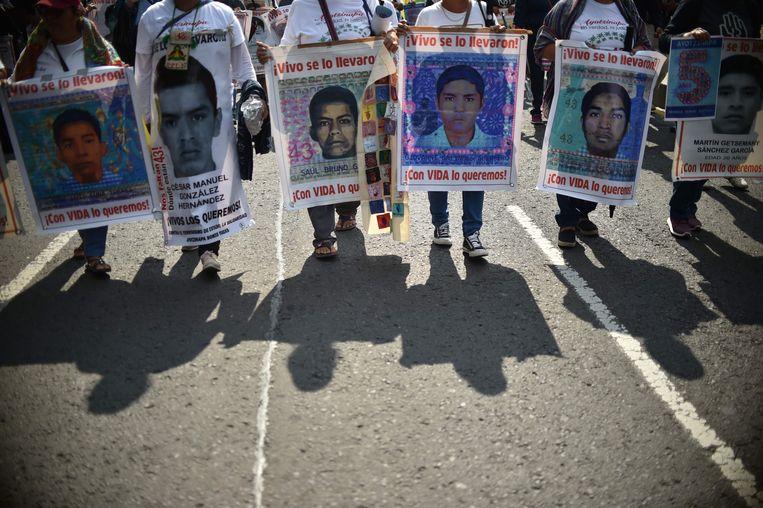 De ouders van de vermoorde studenten houden hun foto's  omhoog terwijl ze opstappen in Mexico-Stad.