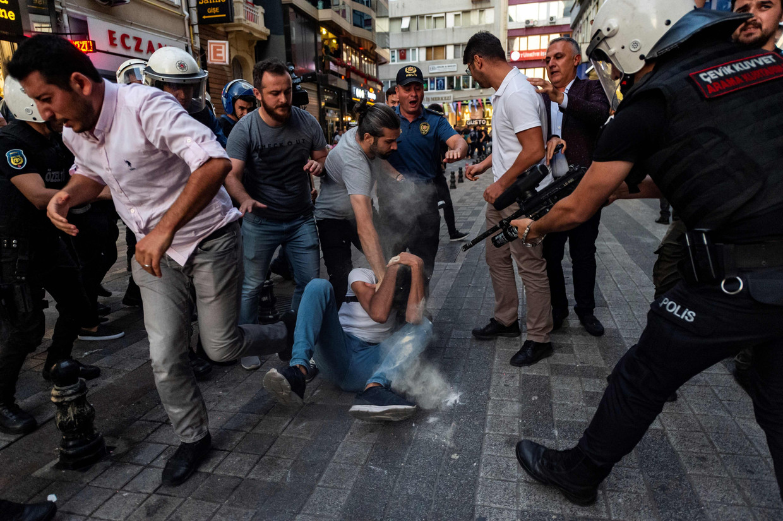 Een agent houdt een betoger onder schot die in Istanbul mee protesteerde tegen het ontslag van Koerdische burgemeesters.  Beeld AFP
