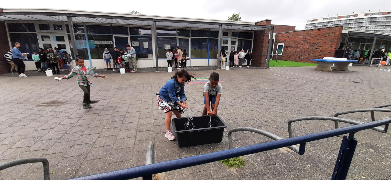 Kinderen rennen om het hardst om een teil water te vullen op het plein van Magistraal, de school die als Middelburgse zomerschool fungeert.