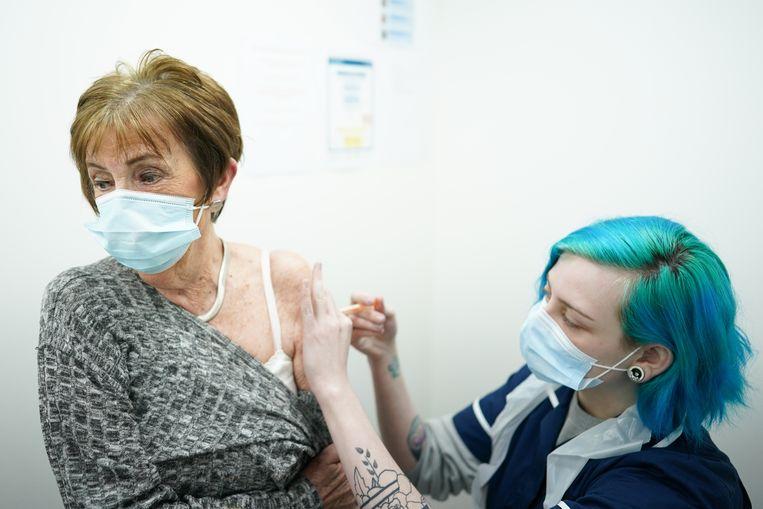 Kay Hatfield (links) kreeg donderdag haar AstraZeneca-prik in een drogisterij in het Engelse Middlesbrough. Het is een van de eerste drogisterijen in de regio die zijn aangehaakt bij de Britse vaccinatiecampagne.  Beeld Getty Images
