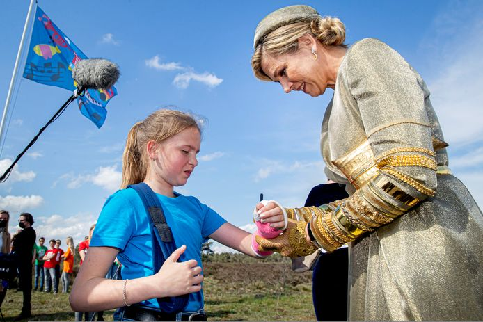 Koningin Maxima zet een handtekening op het gips van  Marilynn.