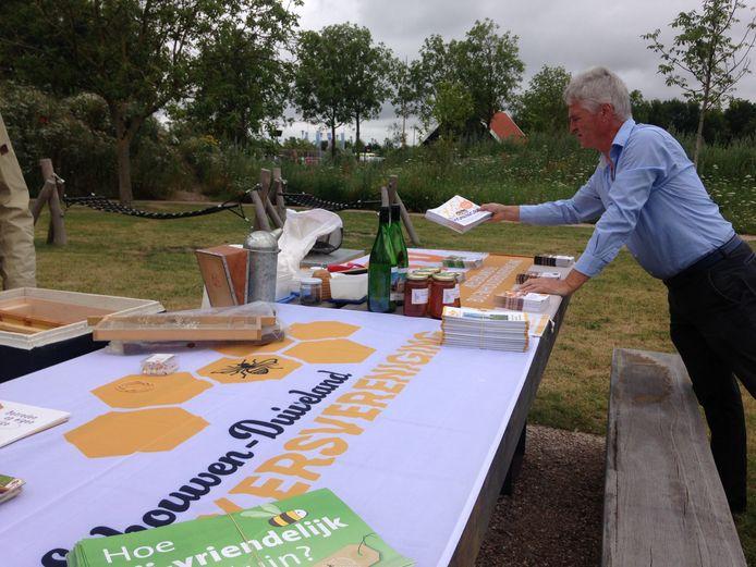 Helle van der Roest richt de presentatietafel in bij het bijenhuisje in Renesse tijdens de Open Imkerdag