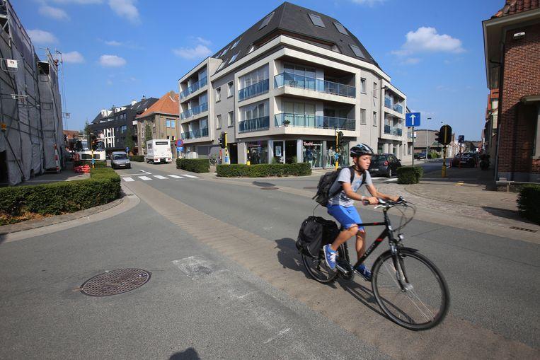 Een jonge fietser passeert het kruispunt van de Kortrijksestraat met de Walstraat.