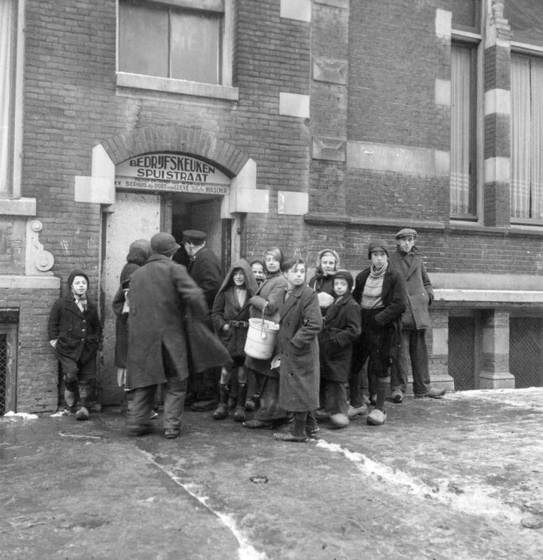 Wachtende mensen bij de Centrale gaarkeuken in de Spuistraat. Beeld Hollandse Hoogte / Nederlands Fotomuseum