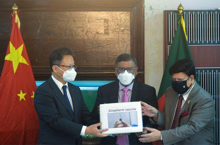 De minister van buitenlandse zaken van Bangladesh, A. K. Abdul Momen (rechts) en de Chinese ambassadeur Li Jiming (links) vorige week bij een ceremonie ter gelegenheid van de aankoop van 500.000 Chinese Sinopharm-vaccins. Beeld AFP