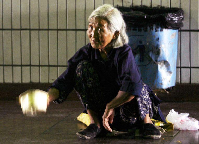 Een vrouw bedelt op een metrostation in Peking. Beeld null
