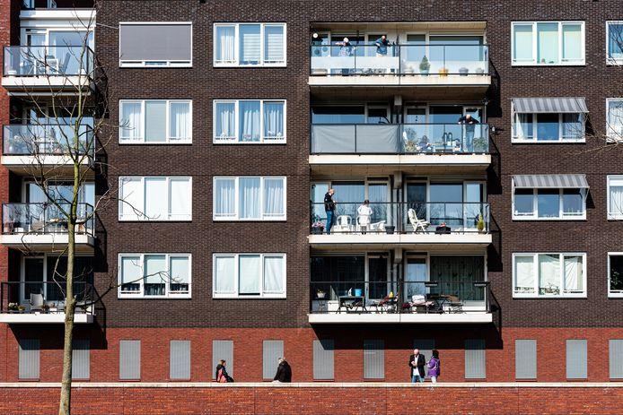 Mirjam Hoogendoorn (paarse jas) houdt een serenade voor tachtigjarige moeder Leny. Die staat op het balkon op de vierde etage.