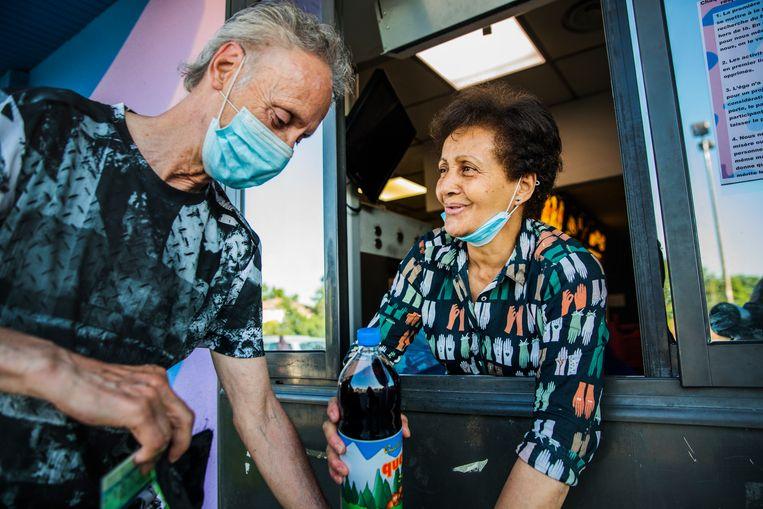 Vrijwilliger Mona hangt uit het raam van de drive-inbalie en stopt iedereen die langskomt  met een glimlach flink wat toe. Beeld Aurélie Geurts