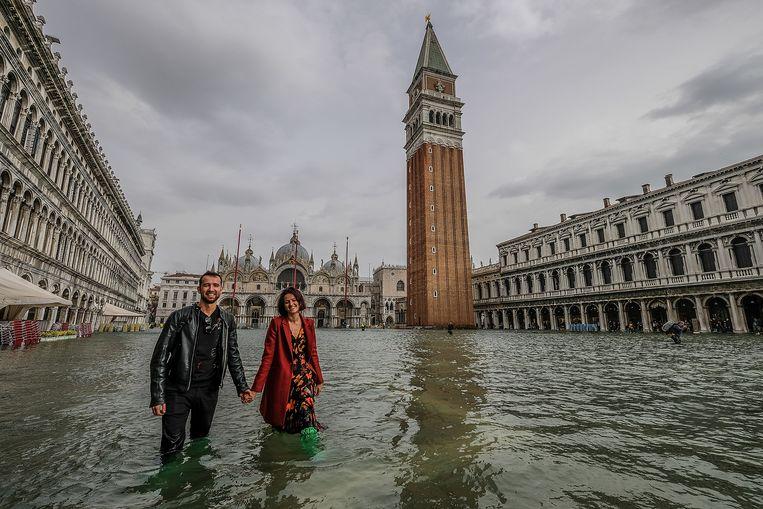 Toeristen staan tot aan hun knieën in het water op het San Marcoplein. Beeld Getty Images