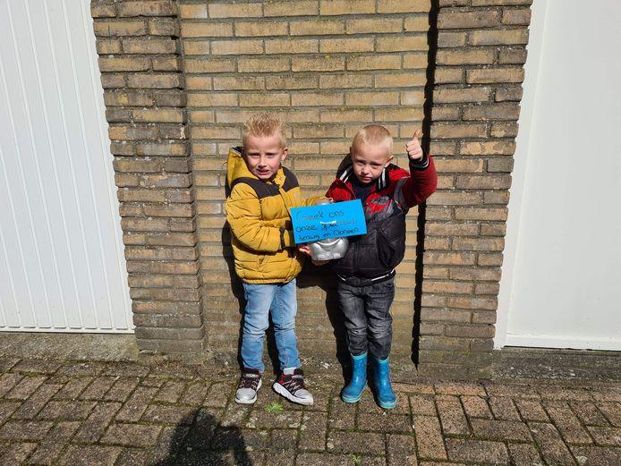 'Geef ons onze speeltuin terug en doneer!' staat op een briefje dat hier omhoog wordt gehouden door Jay Deijkers (l) en Joris Tol.