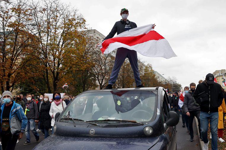 Een demonstrant in de straten van Minsk zwaait met de voormalige Wit-Russische vlag, op 25 oktober 2020. Beeld AFP