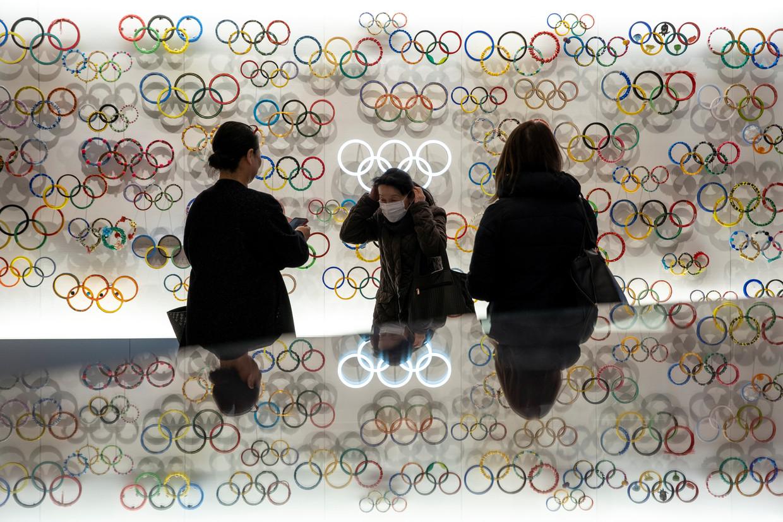 Bezoekers van het Olympisch Museum in Tokio dragen maskers in een poging zichzelf te beschermen tegen het coronavirus.  Beeld Reuters