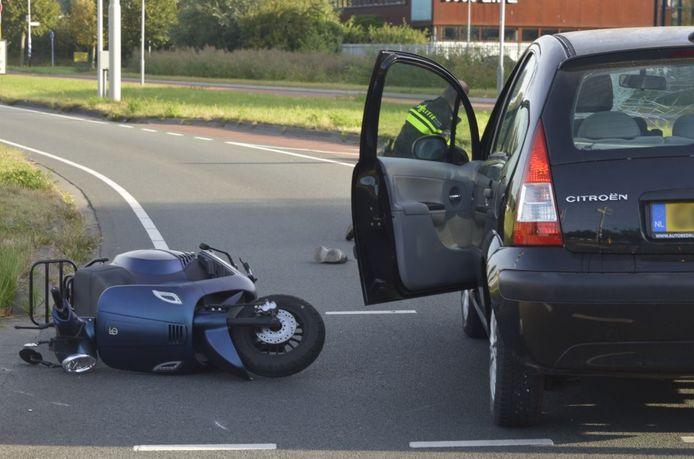 Scooterrijder gewond na botsing met auto in Breda. De scooter ligt op het wegdek.
