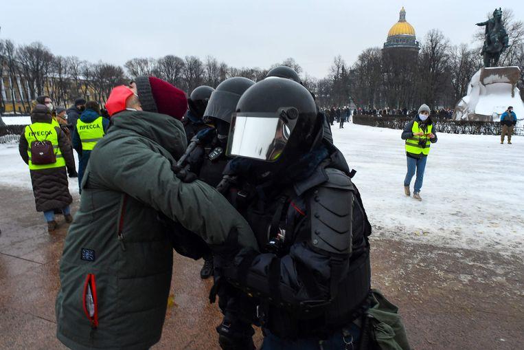 De politie arresteert een man tijdens de protesten in Sint-Petersburg.   Beeld AFP