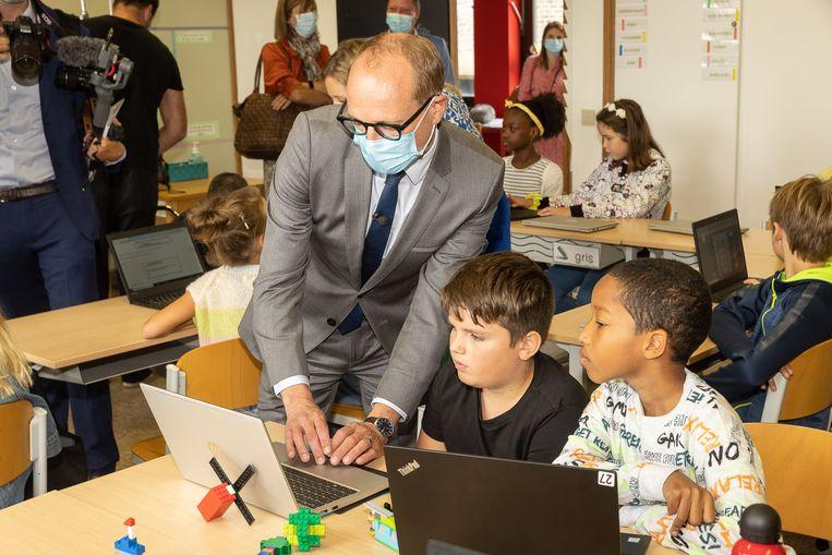 Minister Ben Weyts (N-VA) op bezoek in een school in Merelbeke. Ook hij dringt aan op minder strikte regels. 'Ik begrijp dat men voorzichtig wil zijn en niet voor 200 procent zeker is. Maar als er twijfel is, geef dan het voordeel van de twijfel aan onze kinderen.' Beeld BELGA