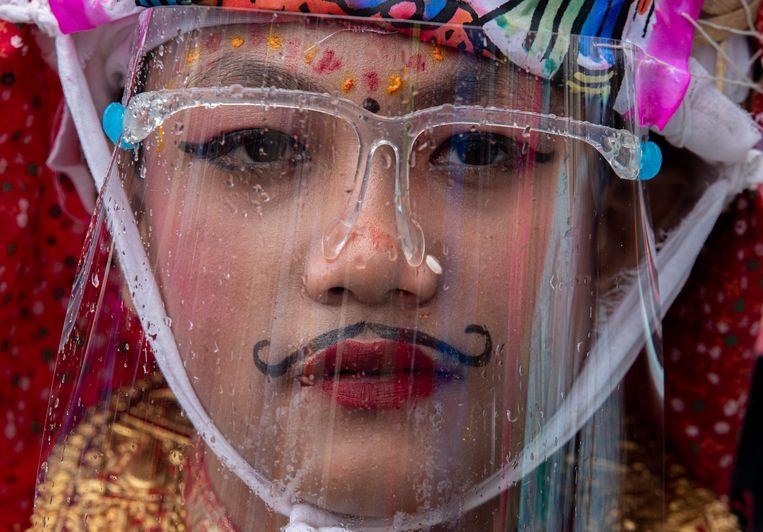 Een jongen in klederdracht en met een beschermend gezichtsmasker op neemt in Nepal deel aan Gai Jatra, het koeienfestival. Hindoes staan in deze periode stil bij familieleden die in het afgelopen jaar zijn overleden. Binnen het hindoeïsme gelden koeien als heilige dieren, die de ziel van overlevenden helpen de hemel te bereiken.  Beeld EPA