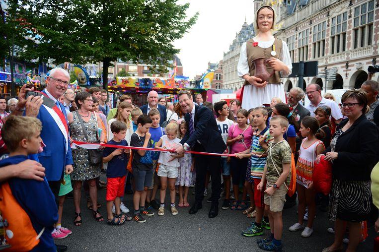 Schepen Dirk Vansina knipt samen met enkele kinderen het lint door, terwijl reuzin Fiere Margriet toekijkt.