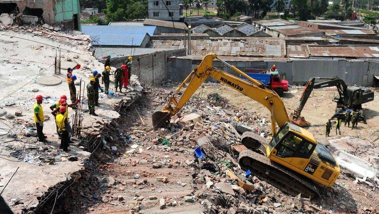 Reddingswerkers zijn bezig bij het ingestorte gebouw in Bangladesh Beeld AFP