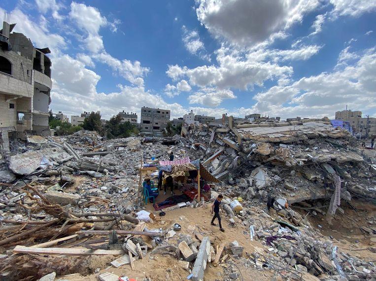 Een Palestijnse jongen loopt langs verwoeste huizen na Israëlische luchtaanvallen.   Beeld REUTERS