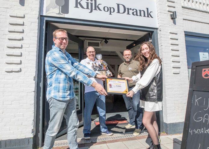 Martin Kuper geeft de cheque aan Britt Janssen. Op de achtergrond Patric Amants (links) en Marco Wagenaar.