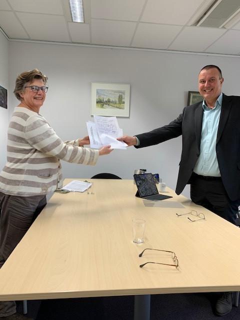 Nelleke van Wijk overhandigt de petitie van de Gemullehoekenweg aan de Oisterwijkse verkeerswethouder Dion Dankers