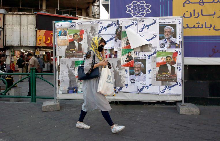 Een vrouw loopt langs verkiezingsaffiches in Teheran. Op 18 juni zijn er presidentsverkiezingen in Iran.  Beeld EPA