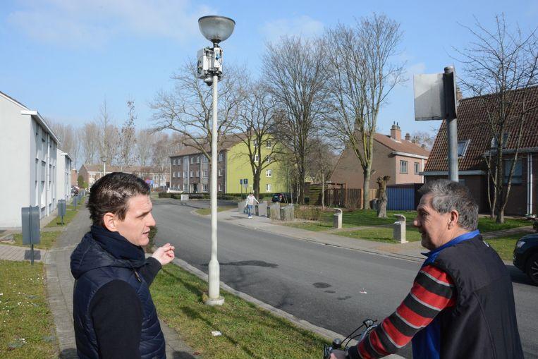 Schepen Filip Kegels legt een buurtbewoner uit dat een camera iedereen in beeld brengt in de omgeving van de sorteerstraat.