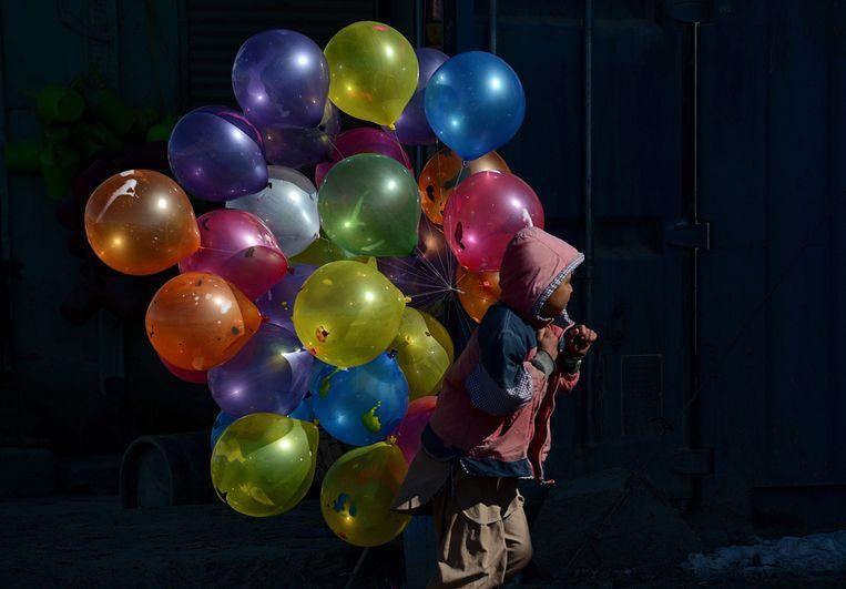Een Afghaanse jongen loopt op straat met ballonnen in Kabul. Beeld AFP