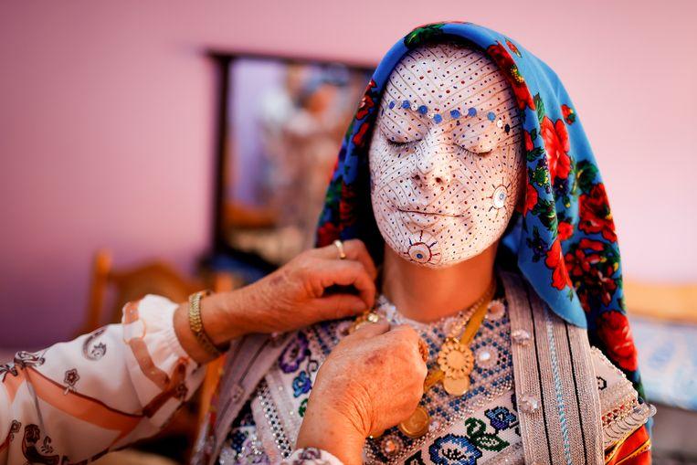 Ze gaat trouwen. Sellma Demirovic uit Donje Ljubinje in Kosovo wordt door haar familie in een traditionele jurk geholpen. Haar gezicht is zo opgemaakt dat het ongeluk op deze belangrijke dag geen kans heeft. Beeld EPA