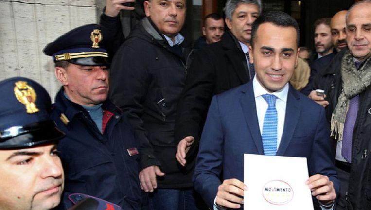 Partijleider Luigi Di Maio laat het symbool van zijn partij zien Beeld reuters