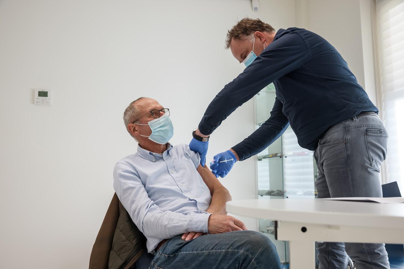 Breda - Dhr. Simons krijgt een prik van AstraZeneca bij huisartsenteam Ginneken van dokter André van den Broek.