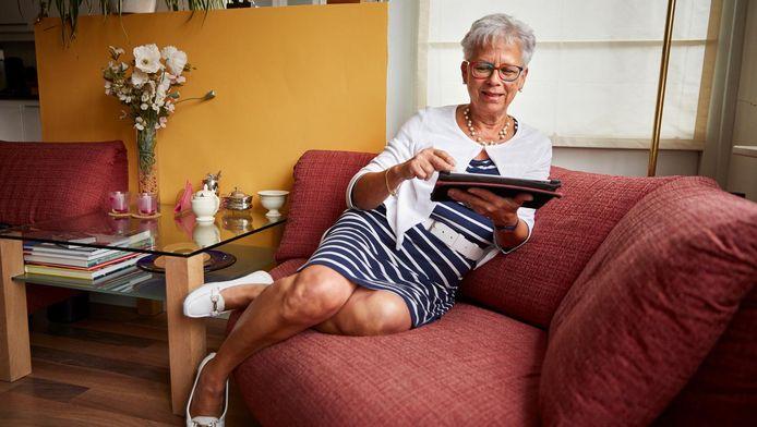 Katy Ecury thuis op de bank met haar tablet waarmee zij via de app Klup in contact komt met onder andere haar vriendin Gerry-Ann Schoester.